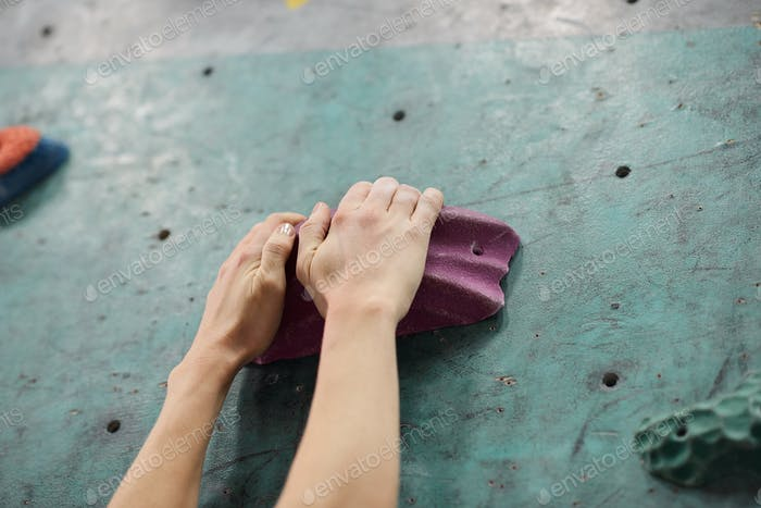 Two hands of sportswoman grabbing one of artificial rocks on climbing equipment