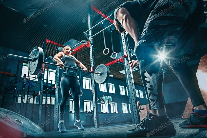 Fit junge Frau Heben Langhanteln trainieren in einem Fitnessstudio