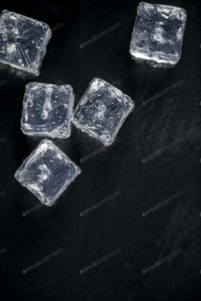 Ice cubes reflection on black table background