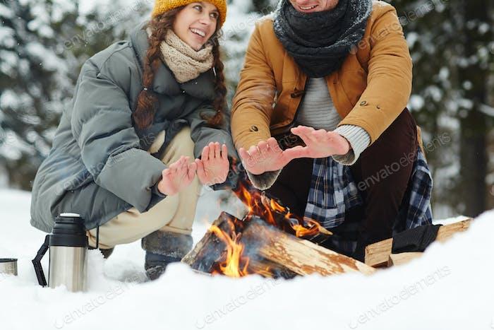Reisende, die sich durch Feuer erwärmen
