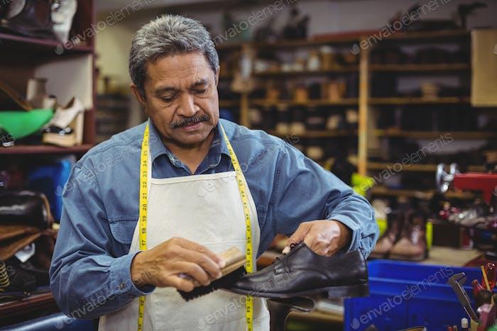 Shoemaker polishing a shoe