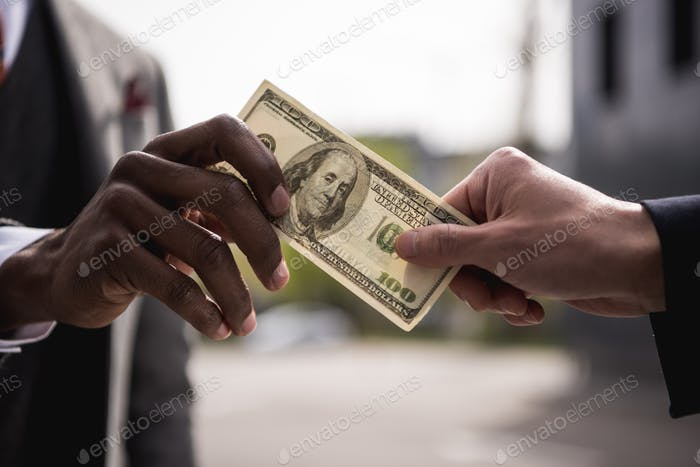 anonymous businessmen hands holding one hundred dollars banknote outdoors