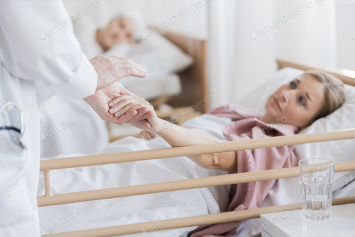 Woman holding doctor's hand