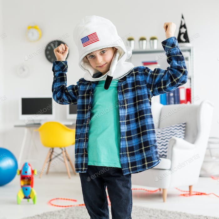 Boy poses in a toy helmet