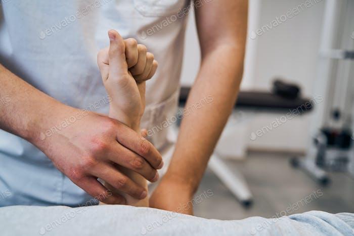 Pediatric physiotherapist in uniform checks girls arm on massage bed closeup. Professional therapist