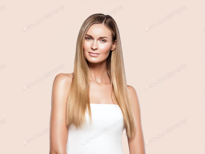 Beautiful woman long hair blonde natural portrait with beauty makeup. On beige.