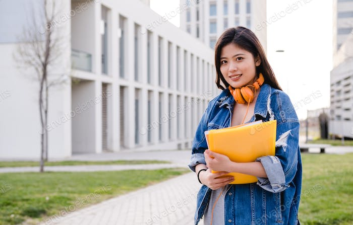 Portrait of an Asian student standing outdoors on college campus. Education concept