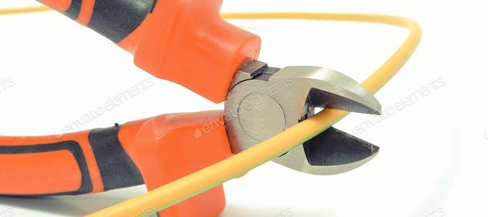 Metallzangen schneiden Elektrokabel auf weißem Hintergrund. Technologie-Konzept