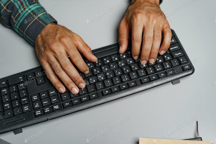 Black man hands typing on computer keyboard