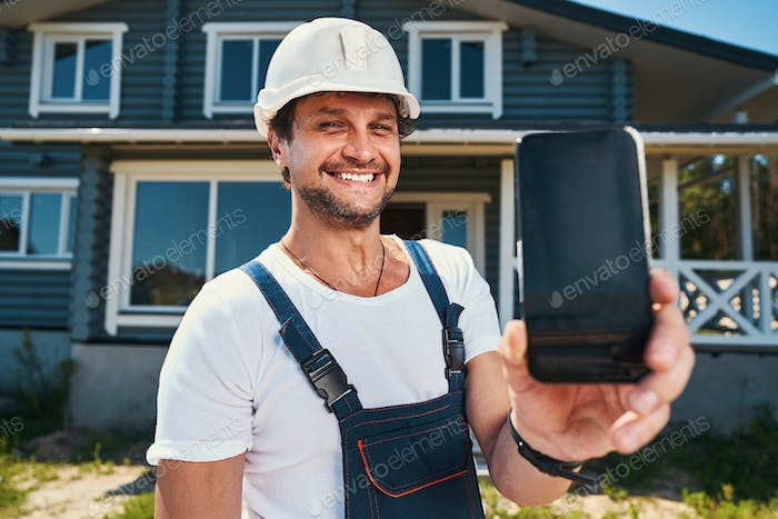 Proud housebuilder showing phone cover in hand