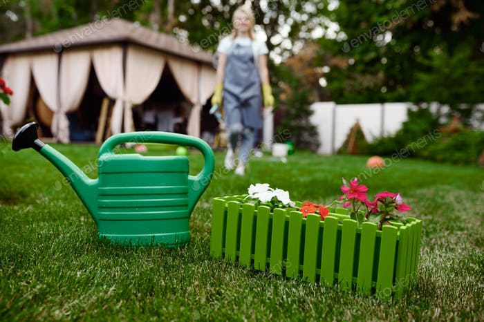 Watering can in the garden, gardener on background