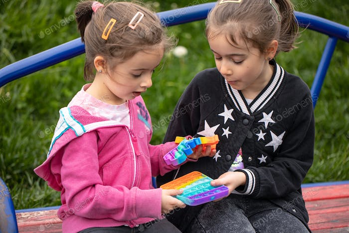 Little girls play with a colorful anti-stress toy pop it.