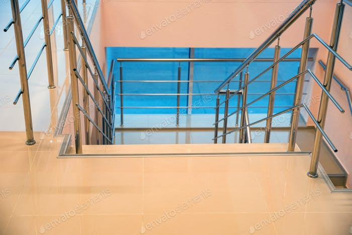 Modern beige office staircase with the chrome handrails