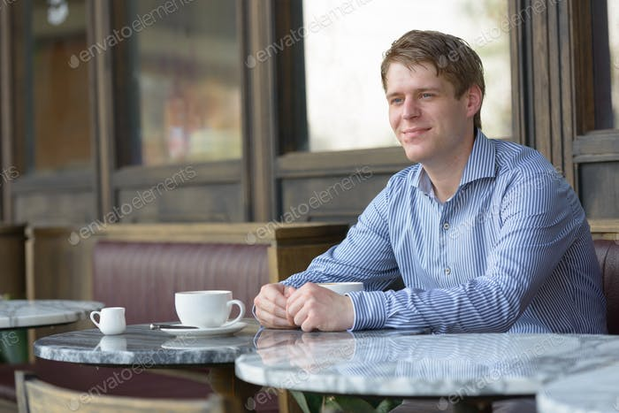 Young blond businessman thinking at the coffee shop outdoors