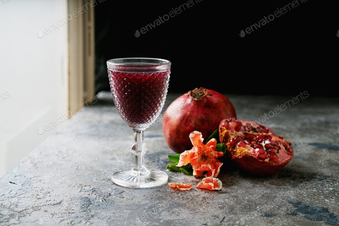 Pomegranate juice and fruits with flowering branches
