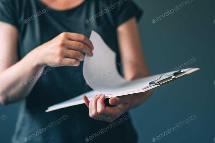 Casual erwachsene weibliche Lesen von Notizen aus Notizblock Papier