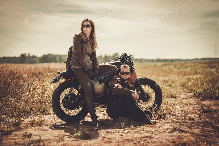 Stylish cafe racer couple on the vintage custom motorcycles in a field
