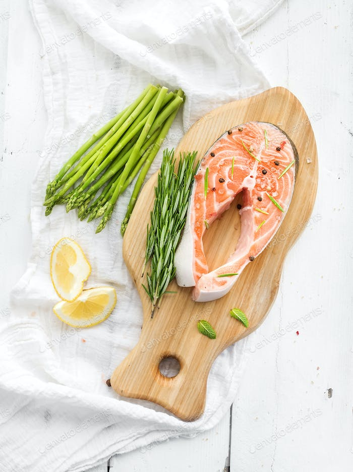 Raw salmon steak with asparagus, lemon, spices and rosemary