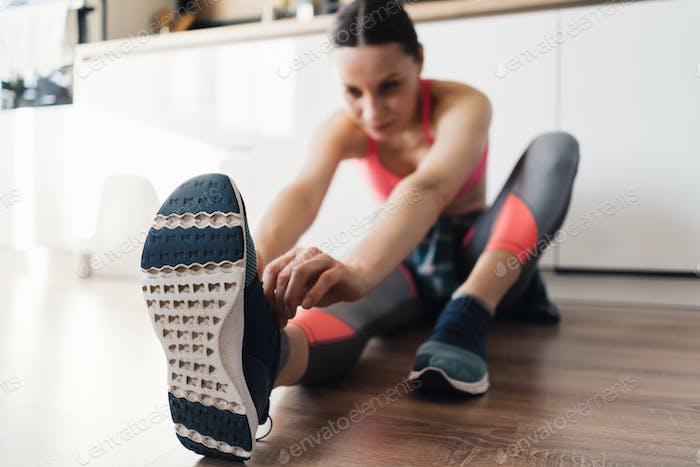 Frau binden ihre Sportschuhe beim Sitzen auf dem Boden