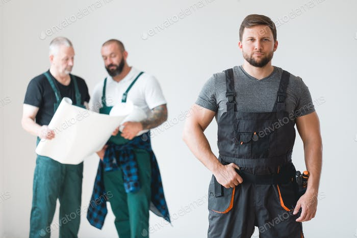 Group of three builders preparing for remodeling of the apartment