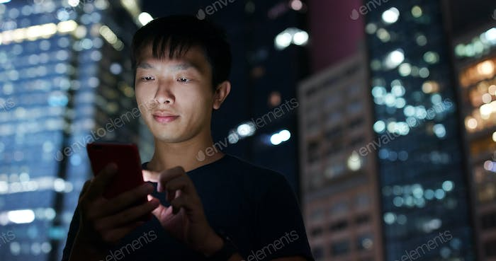 Man use of smart phone in city at night