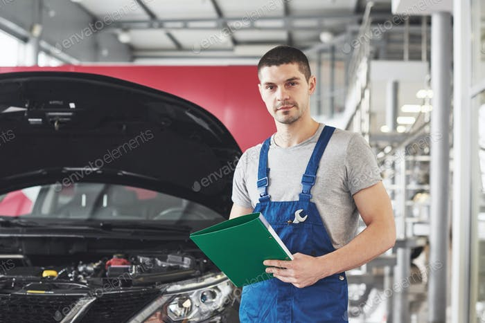 maintenance and people concept - auto mechanic man or smith with clipboard at workshop