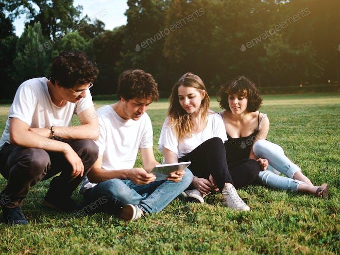 gran grupo de estudiantes que estudian en un parque con tabletas digitales