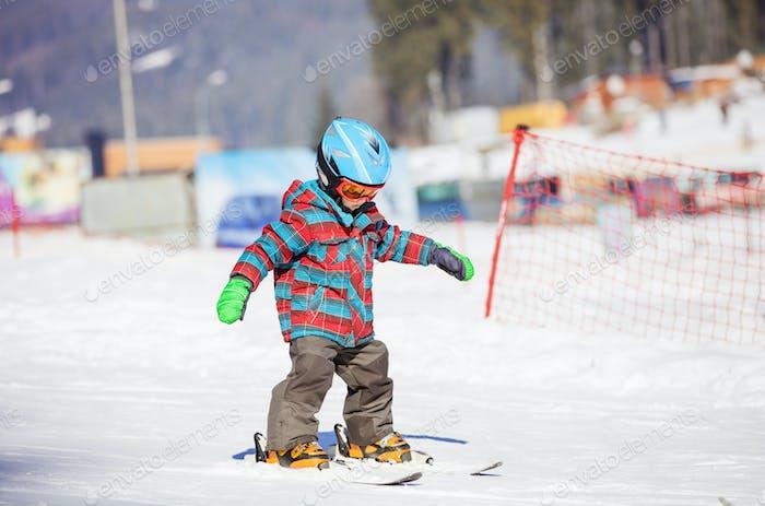 Niño Pequeño esquiando cuesta abajo