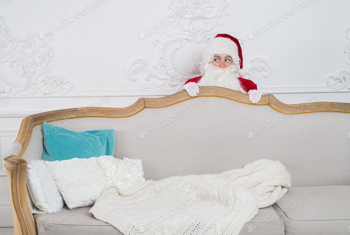 Santa Claus hiding behind a sofa over home interior