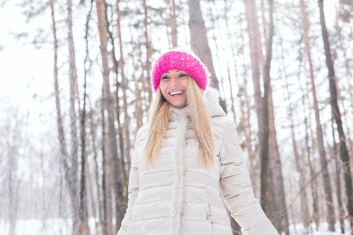 Young pretty woman throwing snow in the air in winter holidays