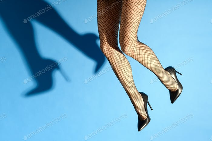 Falling legs of a woman wearing sexy black fishnets and stiletto
