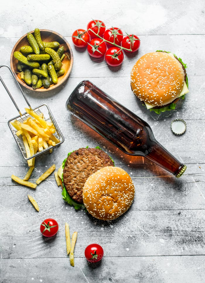 Burgers with beer in a bottle,gherkins and fries.
