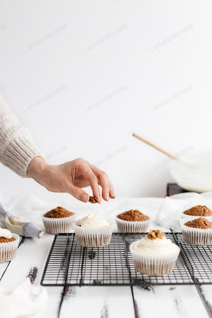 Woman Topping Carrot Cupcakes with Nuts in Kitchen
