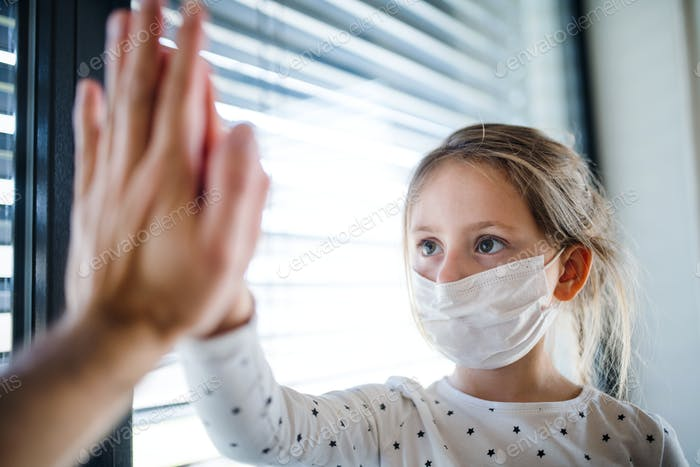 Small girl with unrecognizable mother indoors at home, giving high five