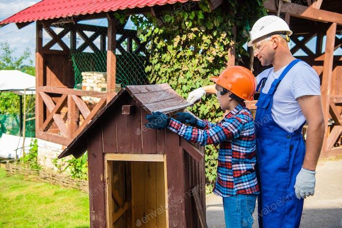 Junge, Teenager mit Schutzhelm beschäftigt, um das Hundehaus mit seinem Vater zu reparieren. Vater
