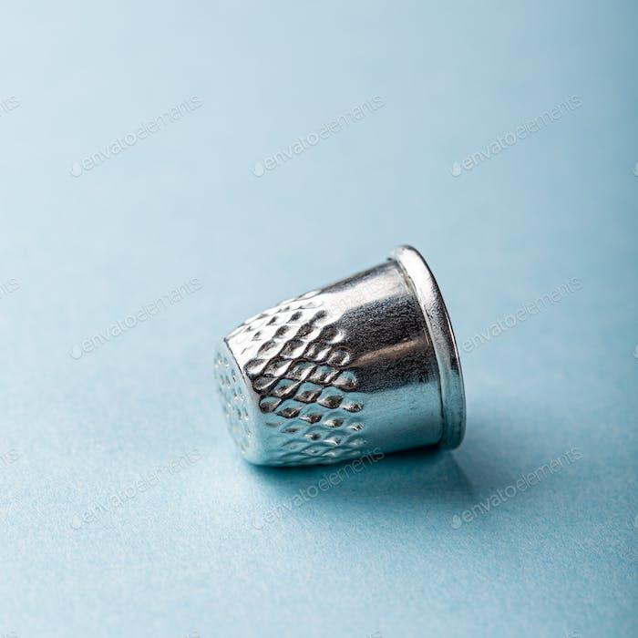 vintage silver thimble on blue