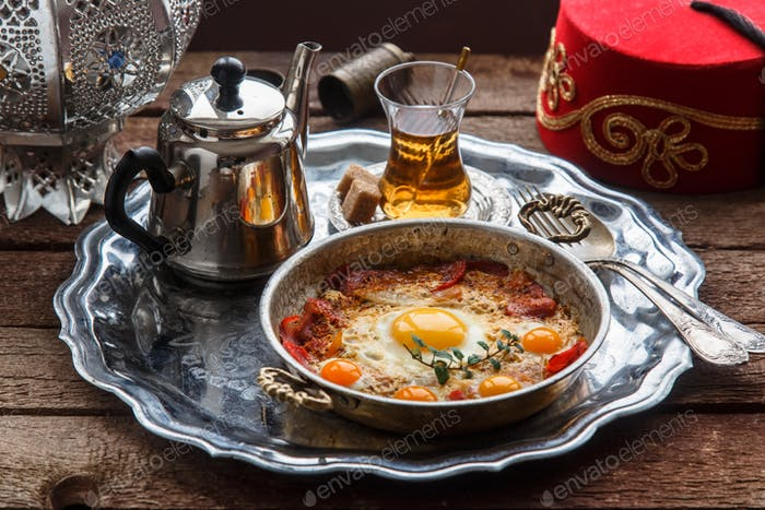 Fried egg with cured meat, traditional turkish breakfast, served in metal dishware, rustic
