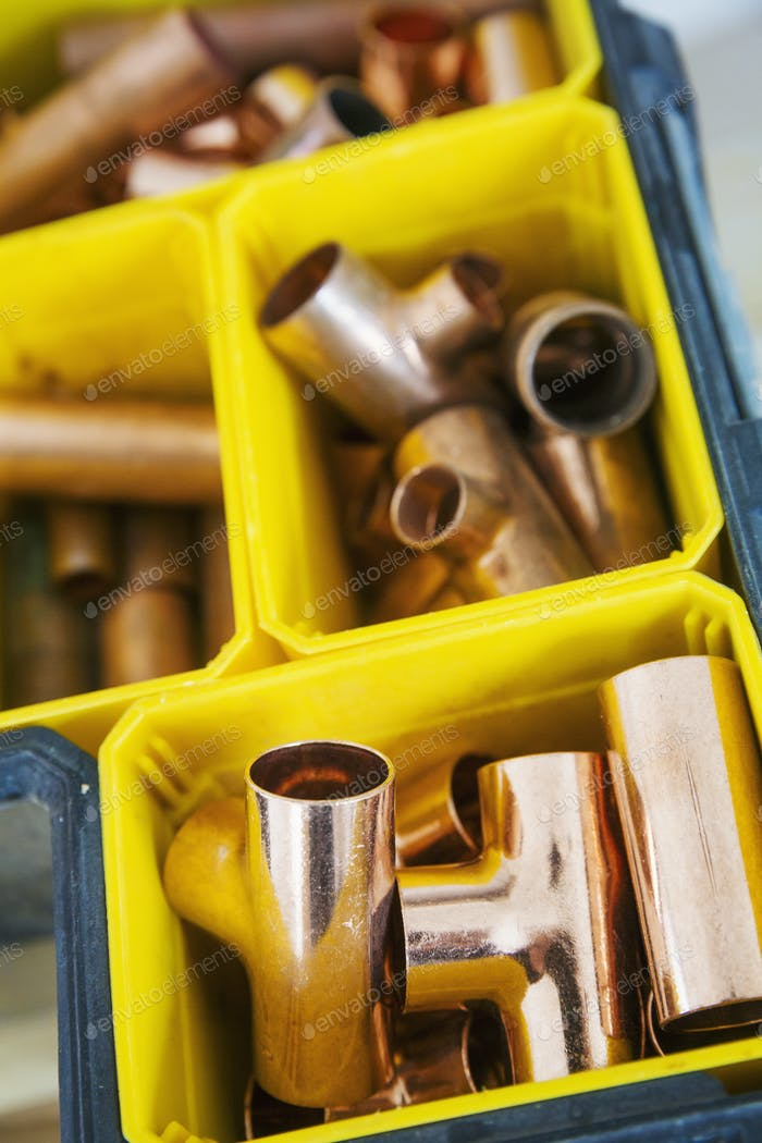 Close up of plastic boxes with parts of copper pipe.