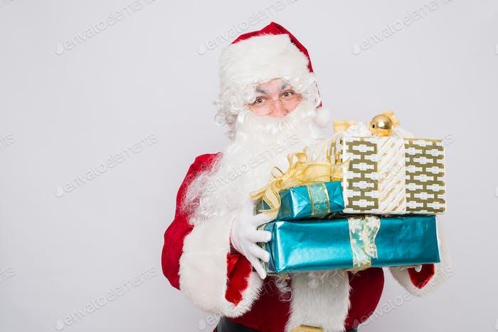 Santa holding many Christmas gifts