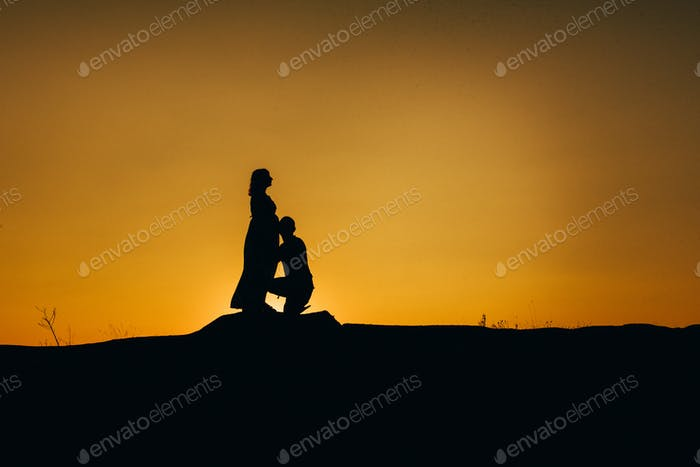 Silhouetten einer glücklichen jungen glücklichen Familie gegen einen orangefarbenen Sonnenuntergang
