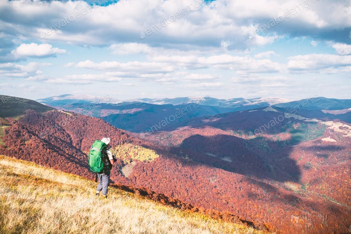 Backpacker at sunny autumn meadow with orange beech trees