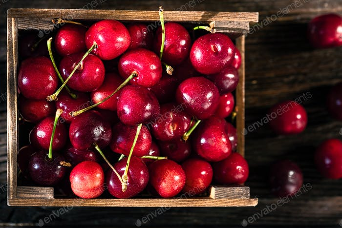 Fresh sweet cherries in a wooden box top view