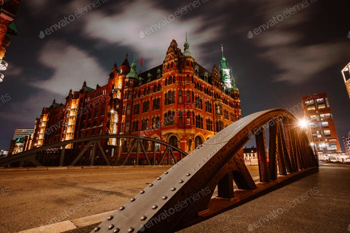 Old Speicherstadt in Hamburg illuminated at night. Arch bridge and historical buildings. Warehouse
