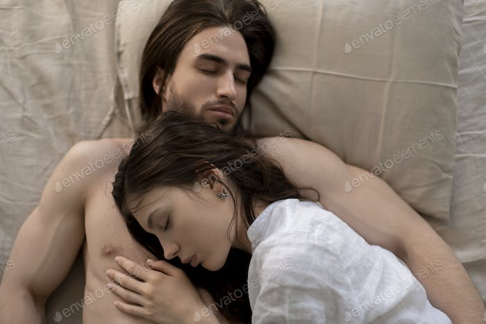 Woman sleeping in Bed,  while her man is caressing her face