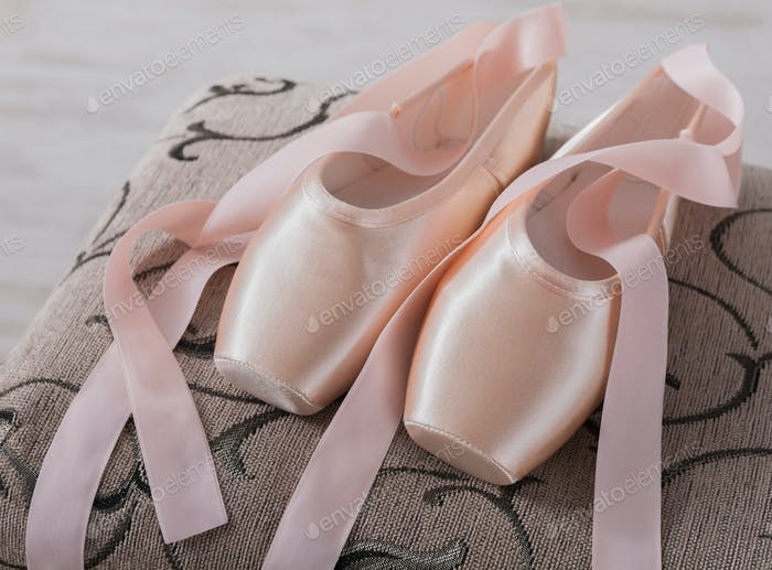 Pink ballet pointe shoes on chair background