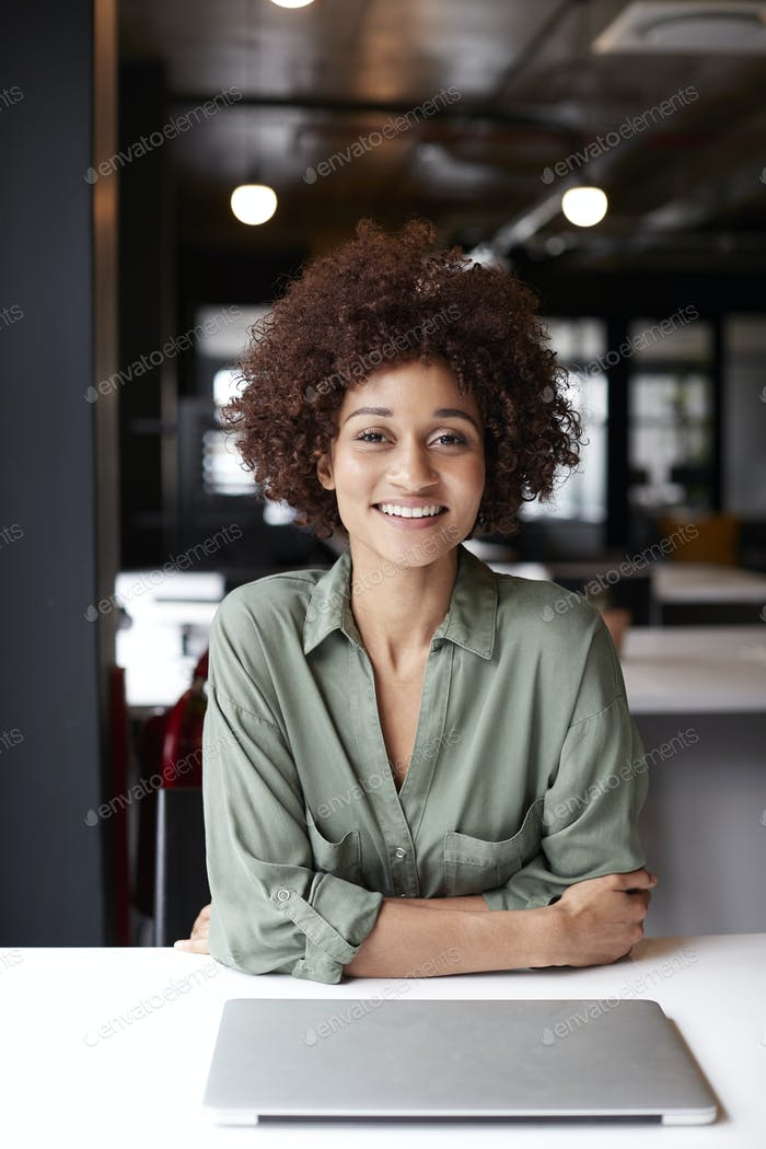 Millennial black female creative sitting at desk in an open plan office smiling to camera, vertical