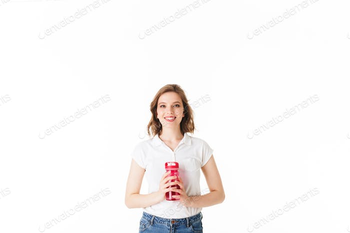 Young beautiful lady standing with pink sport bottle in hands and happily looking in camera
