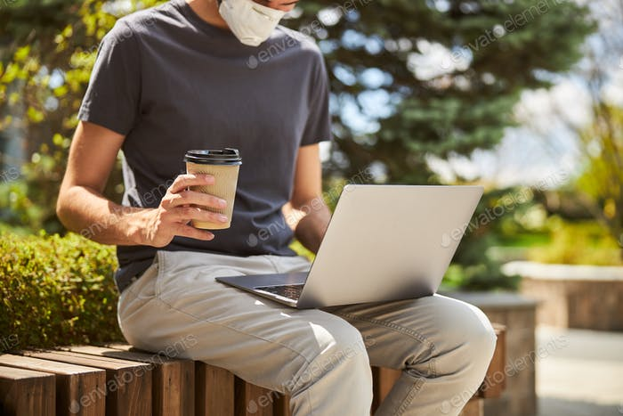 Man with a coffee cup working remotely
