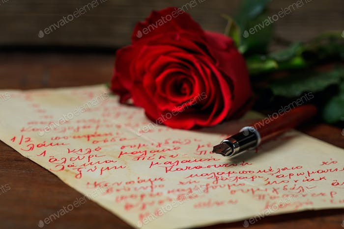 Red rose and an ink pen on a letter