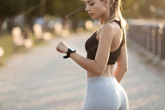 Millennial woman working out with fitness bracelet
